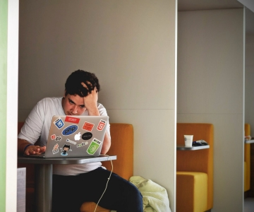 Student holding head behind open laptop
