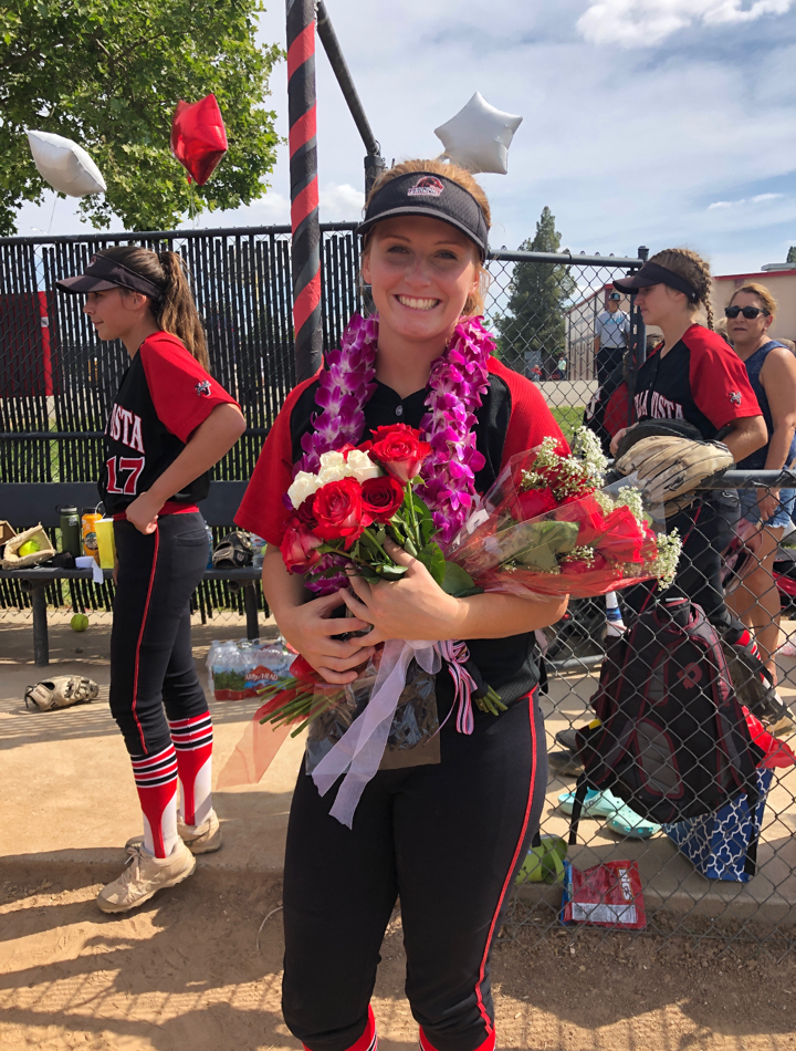 Alexis Detwiler in uniform after game holding roses