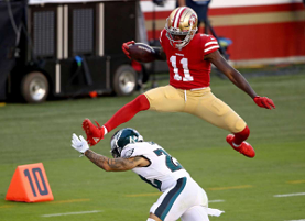 Football player jumping over other player