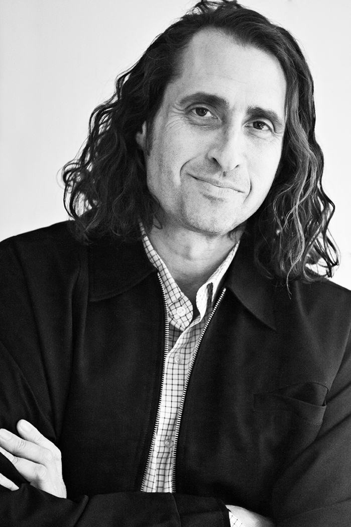 Geoff Siegel portrait, suit jacket, crossed arms, long wavy hair, closed mouth smile