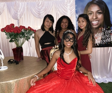 Katelyn Vengersammy in fancy red dress with three girl cousins and red roses behind her for Debut party.