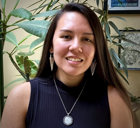 Photo of Leonor Bright, long straight dark hair, silver dangly earrings and necklace, smiling