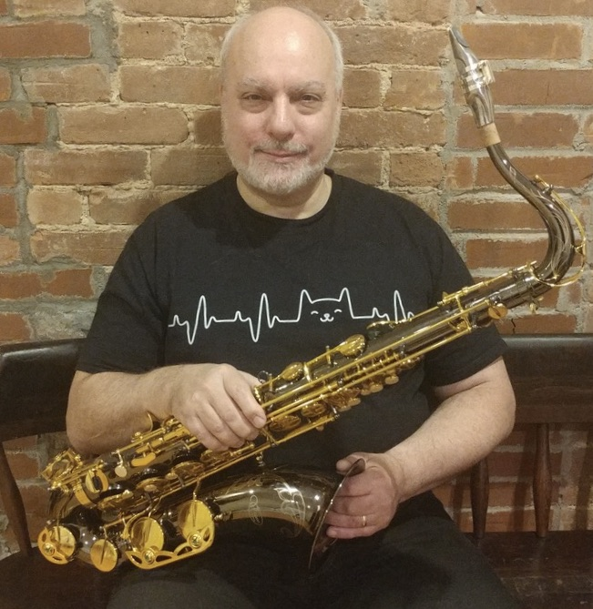 Norbert Stachel with saxophone, sitting white beard, small smile