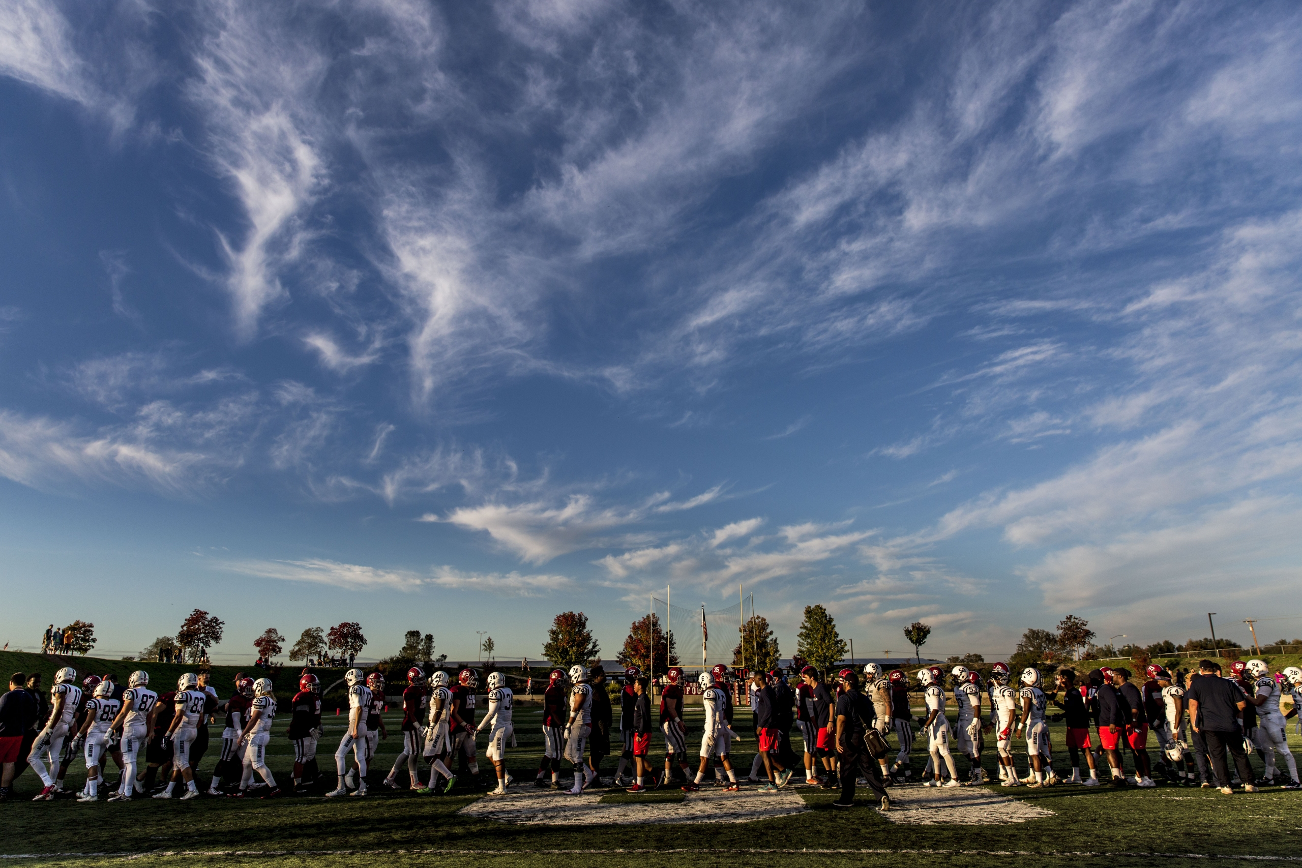 Sunny sky and football players lined up in distance, cloud patterns in wavy shapes